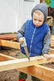 Little studious boy sawing a wooden board. Home construction. Li Stock Photography