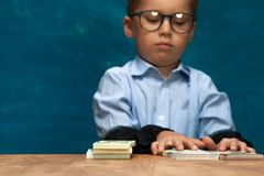 Little stylish boy counting money at workplace. Portrait of little stylish boy sitting at workplace, counting money. Cute child wearing eyeglasses imitating Royalty Free Stock Image