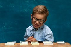 Little stylish boy counting money at workplace. Portrait of little stylish boy sitting at workplace, counting money. Cute child wearing eyeglasses imitating Royalty Free Stock Images