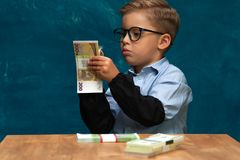 Little stylish boy counting money at workplace Royalty Free Stock Image