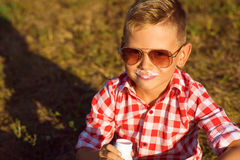 Little stylish boy in sunglasses is sitting on the meadow drinking yogurt stock photo