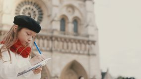 Little stylish girl in beret drawing the picture in notebook near the Notre Dame in Paris, France, doing her hobby. Cute child enjoying the beautiful view of stock footage