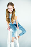 Little stylish grimace girl sitting on chair Royalty Free Stock Images