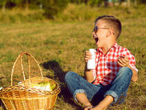 Little stylish kid wearing trendy checked shirt and jeans is hav. Ing fun on the picnic. He is drinking yogurt and has milk moustache over his mouth. Dairy Stock Photos