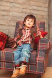 Little stylish toddler sitting in armchair stock image
