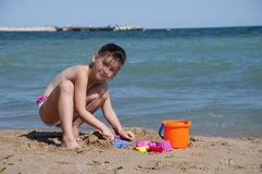 Little summer girl. Little girl play on the sea coast , draws a hearth on the sand stock images