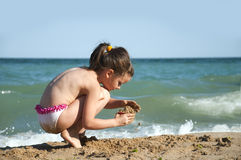 Little summer girl. Little girl play on the sea coast , draws a hearth on the sand stock photography