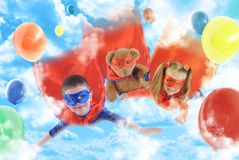 Little Superhero Kids Flying in the Sky. Two young superhero children are flying in the sky with balloons and a teddy bear for a party or rescue concept stock photography