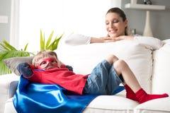 Little superhero resting on sofa Stock Image