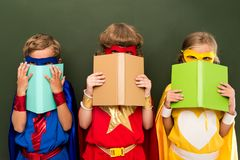 Little superheroes with books. Little superheroes in costumes holding books, chalkboard behind Stock Images