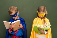 Superheroes reading books. Little superheroes in costumes reading books, chalkboard behind Royalty Free Stock Photo