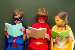 Superheroes reading books. Little superheroes in costumes reading books, chalkboard behind Stock Photo