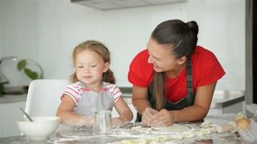Little Supporter is Helping Her Mother To Cook. Mother Shows Her Daugher How To Prepare Dough. stock footage