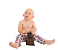 Little surprised baby boy with coffee grinder wearing plaid pants Royalty Free Stock Photos