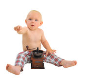 Little surprised baby boy with outstretched hand with coffee grinder wearing plaid pants Royalty Free Stock Photography