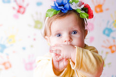 Little surprised baby. Wallpaper with children's handprints on background Royalty Free Stock Image