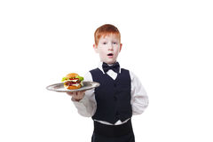 Little surprised boy waiter stands with tray serving hamburger Stock Images