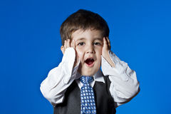 Little surprised businessman, cute little boy portrait over blue Stock Photos