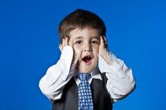Little surprised businessman, cute little boy portrait over blue Stock Photos