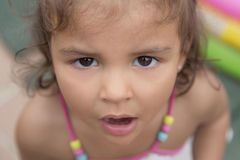 Little surprised girl looking at camera. Close-up of cute surprised girl with open mouth looking at camera. From above Royalty Free Stock Photos