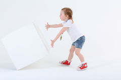 Little surprised girl in shorts pushes large white cube royalty free stock photo