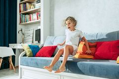 Little surprised teen girl watching tv at home. Little surprised and astonished teen girl watching tv at home. Female kid jumping on sofa Stock Photo