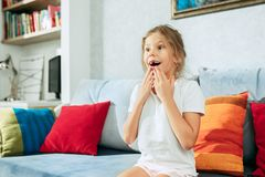 Little surprised teen girl watching tv at home. Little surprised and astonished teen girl watching tv at home. Female kid sitting on sofa Royalty Free Stock Image