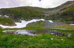 Little swamp under the hill with patch of snow. Lovely springtime nature background Stock Photography