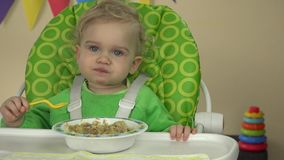 Little girl practice eat gruel with spoon sit on baby chair. 4K
