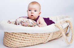 Little sweet girl a baby lying. On a beautiful cushion in a wicker basket, and watch with interest to the side Royalty Free Stock Image