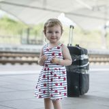 Little sweet girl with a big suitcase on a deserted railway plat. Form Royalty Free Stock Photos