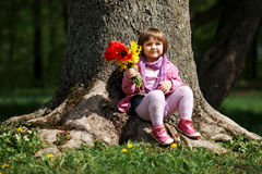 Little sweet girl with flowers. Sitting on big tree in park Stock Photos