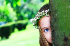 Little sweet girl hiding behind a tree. In a park Royalty Free Stock Photo