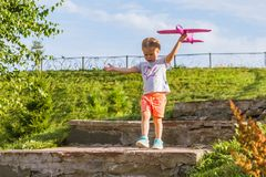 Little sweet girl runs along the stone steps of the park on a sunny summer day with a toy with a pink airplane royalty free stock image