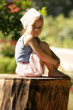 A little sweet girl is sitting on a stump Stock Photography