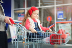 A little sweet girl is sitting in a supermarket shopping cart. Royalty Free Stock Photos