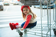 A little sweet girl is sitting in a supermarket shopping cart. Stock Images