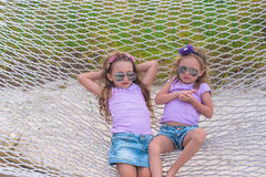 Little sweet girls relaxing in hammock on summer Stock Photo
