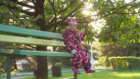 A cute little happy girl sits on a bench and swinging legs under an oak tree. Little sweet little happy girl in a warm pink overall sitting on a green bench and stock video footage