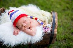 Little sweet newborn baby boy, sleeping in crate with knitted pa. Little sweet newborn baby boy, sleeping in crate with knitted colorful hat in garden, outdoors Stock Images