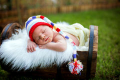 Little sweet newborn baby boy, sleeping in crate with knitted pa. Little sweet newborn baby boy, sleeping in crate with knitted colorful hat in garden, outdoors Royalty Free Stock Images