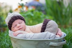 Little sweet newborn baby boy, sleeping in crate with knitted pa. Nts and hat in garden, outdoors in the park Royalty Free Stock Image