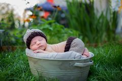Little sweet newborn baby boy, sleeping in crate with knitted pa. Nts and hat in garden, outdoors in the park Stock Photo