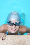 Little Swimmer. Little girl in a gray swimming cap and goggles with a big smile Royalty Free Stock Images