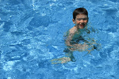 Little Swimmer. Young boy swimming royalty free stock images