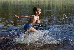 Little swimmer. The joyful boy runs in the waters of a lake, splashing in all directions Stock Image