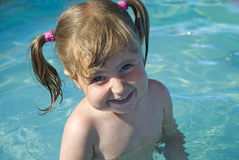 Little swimmer. Nice little girl is standing in the pool and smiling Royalty Free Stock Image