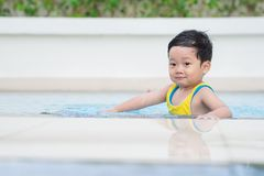 Little swimmer. Little boy sitting in swimming pool Royalty Free Stock Images