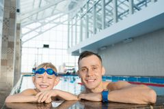 Little Swimmer and His Handsome Coach. Group portrait of cheerful little boy and his handsome coach looking at camera with wide smiles while leaning on edge of Royalty Free Stock Image