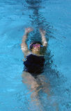 Little Swimmer Under Water. Little girl swimming under water after flip turn at swim meet Stock Photo